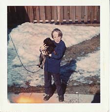 Kevin Pelletier as a small boy with a cute dog in his arms on a snowy day.
